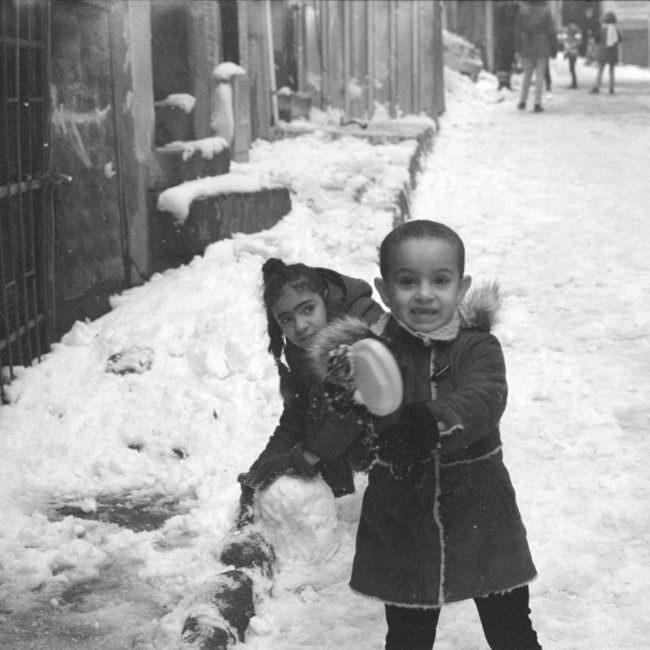 Kinder spielen im Schnee auf der Straße.