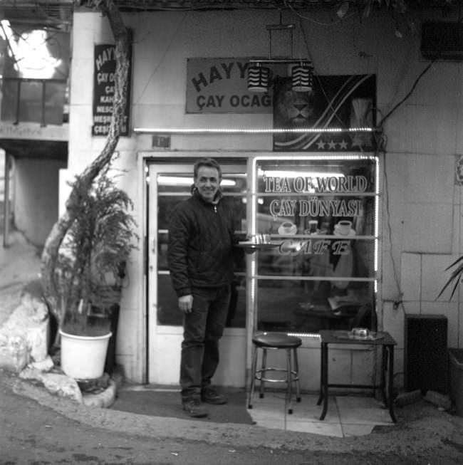 Mann steht vor einem Teeladen.