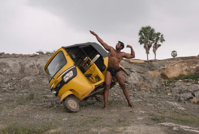 Bodybuilder posiert vor einem Fahrzeug