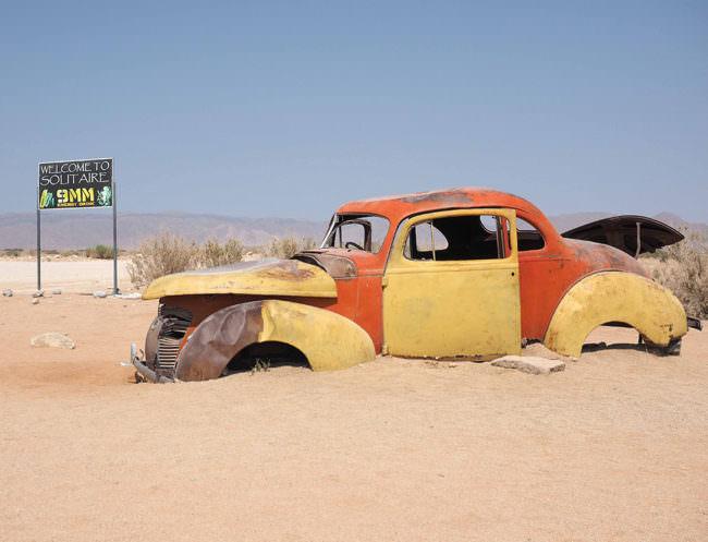 Verrostetes gelb-rotes Auto in einer Wüste.