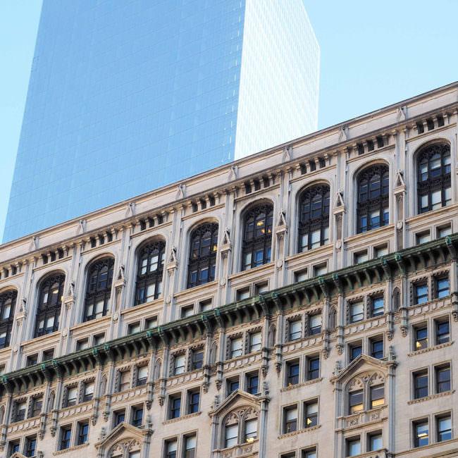 Historisches Gebäude mit vielen Verzierungen, dahinter Wolkenkratzer aus Glas.