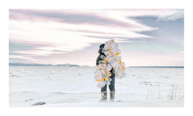 Mann mit Plastikflaschen im Schnee