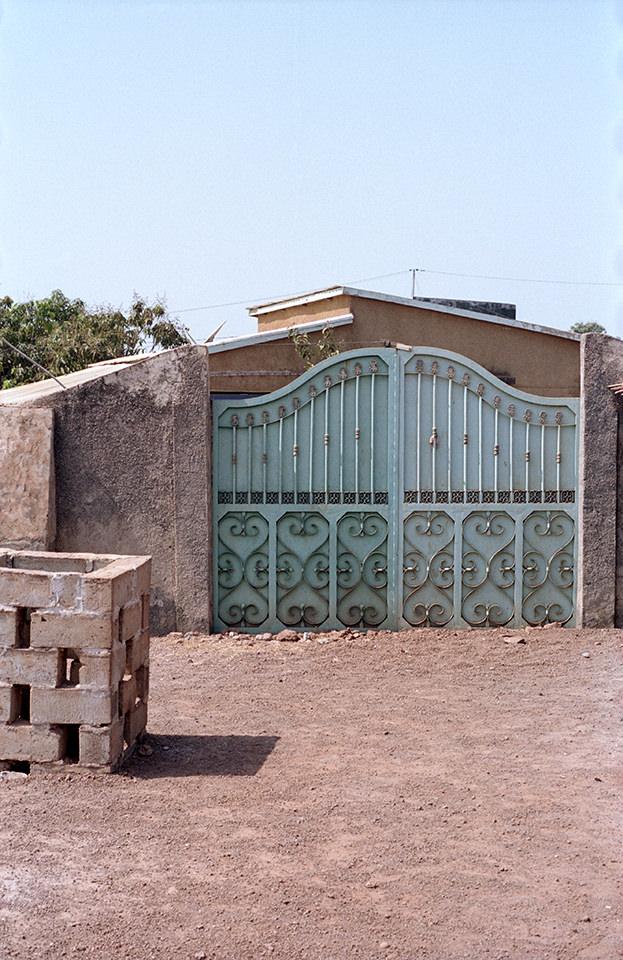 Eisernes, blaues Tor in einer Mauer. Dahinter Umrisse eines Hauses.