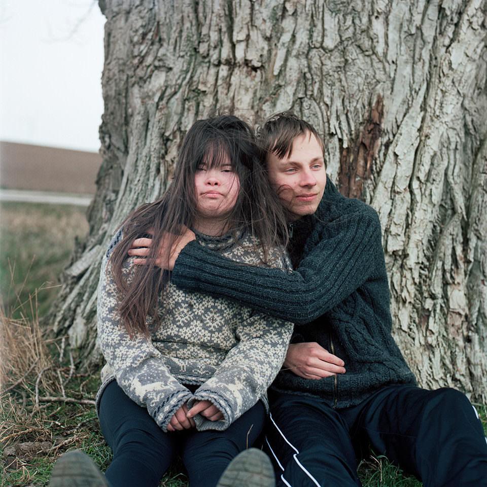 Eine Frau und ein Mann lehnen sitzend an einem Baumstamm
