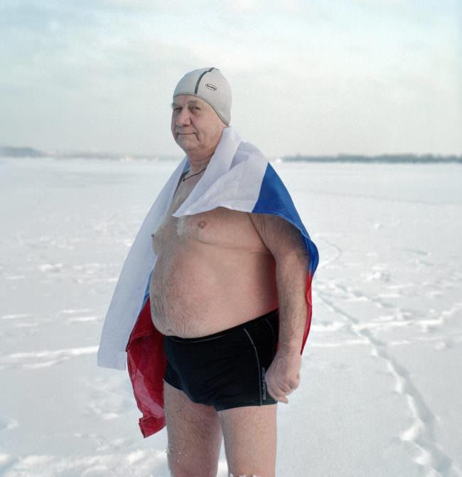 Mann mit Badehose und Handtuch im Schnee