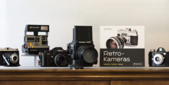 Mehrere ältere Kameramodelle auf einer Holzunterlage. Dazwischen ein Buch mit Titel Repro Kameras.