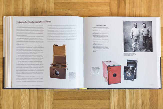Ein aufgeschlagenes Buch auf Holzboden mit Kameraabbildung und Text.