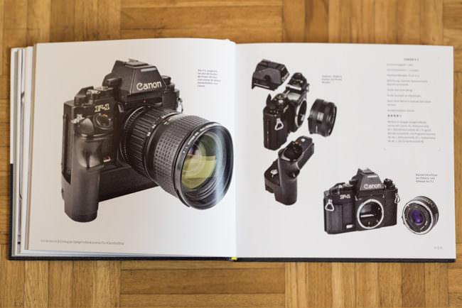 Ein aufgeschlagenes Buch auf Holzboden mit Kameraabbildung.