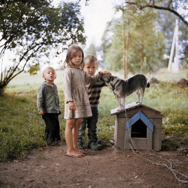 Kinder mit einem Hund an einer Hundehütte