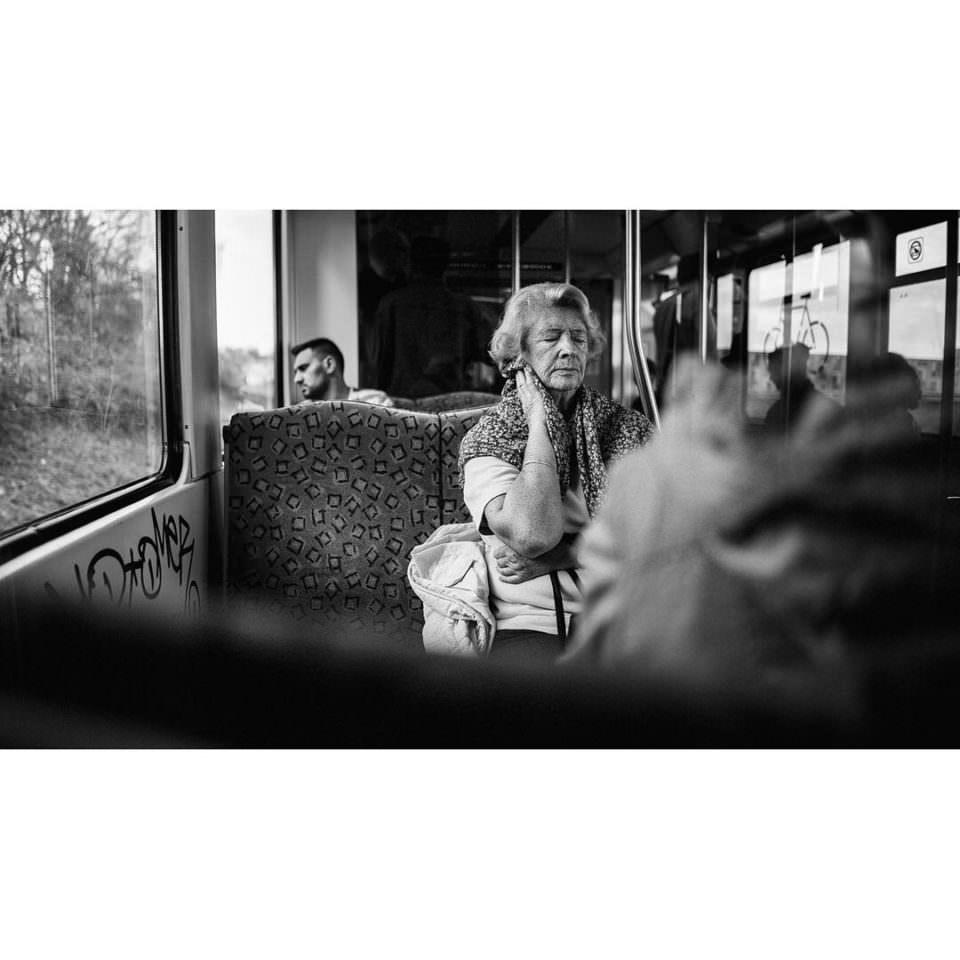 Ältere Dame, die mit geschlossenen Augen in einer Bahn sitzen.
