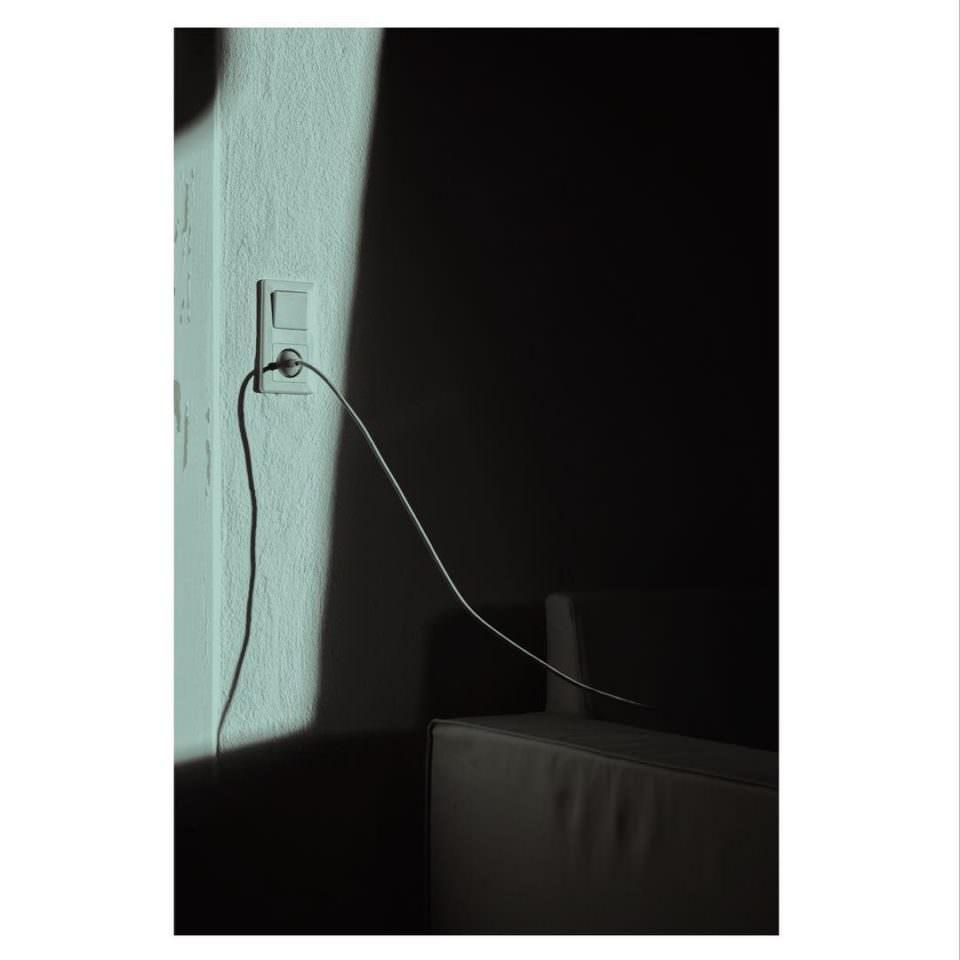 Steckdose mit Kabel, das daraus führt in starkem Sonnenlicht mit Schattenwurf.