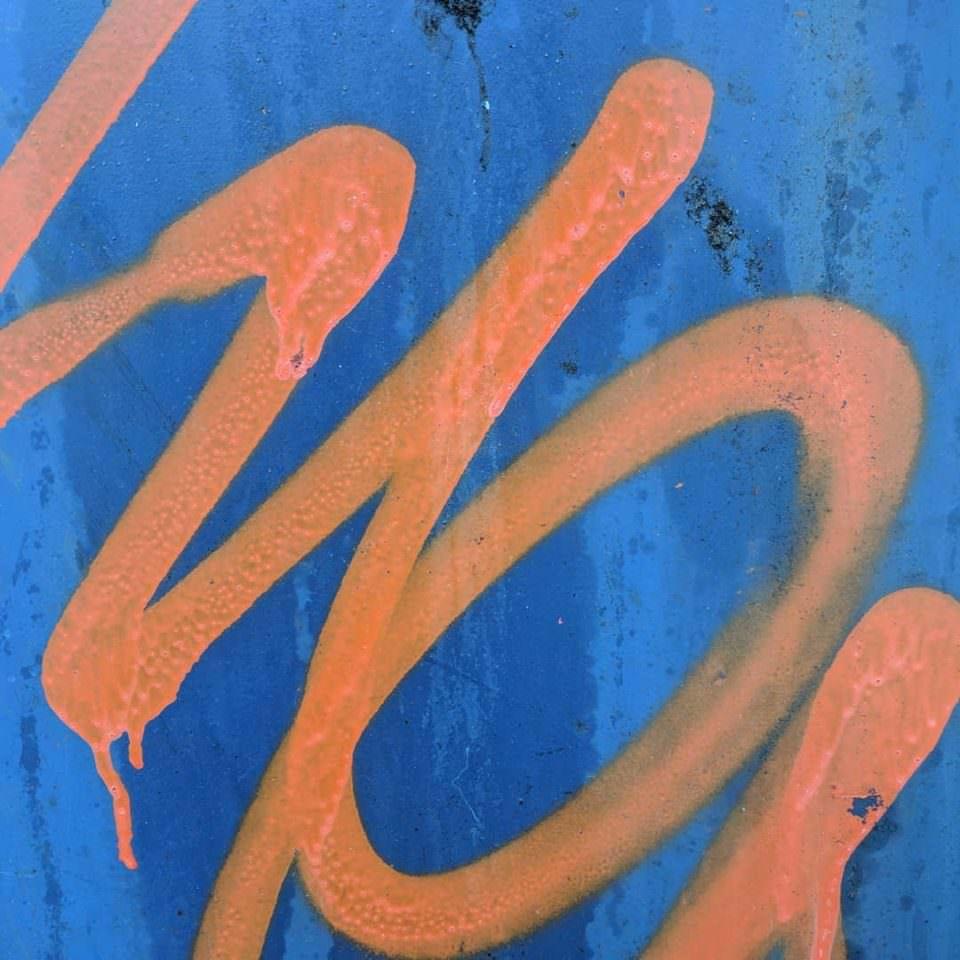 Detail eines orangen Graffiti auf blauem Grund.