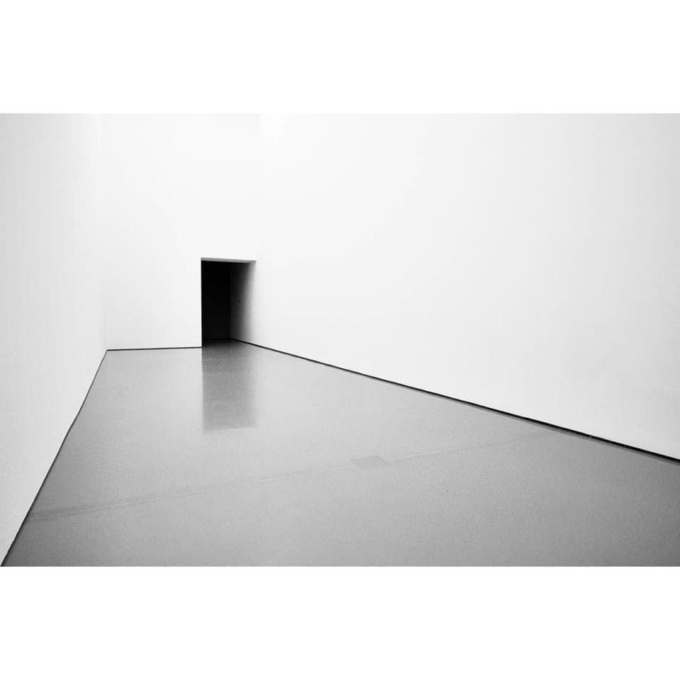 Weißer Raum mit dunkler Türöffnung.
