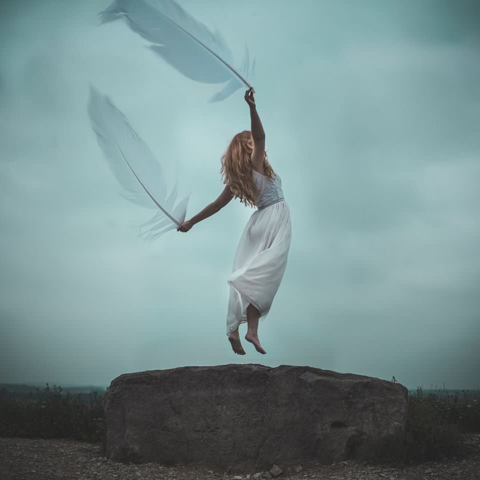 Eine Frau mit zwei großen Federn beginnt zu fliegen
