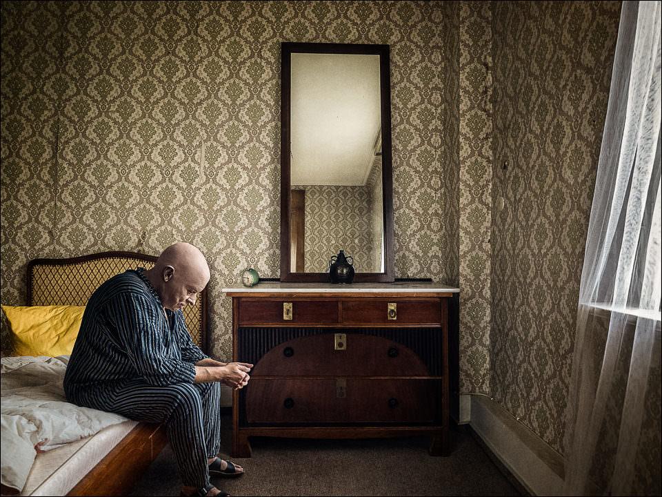 Ein Mann sitzt auf einem Bett