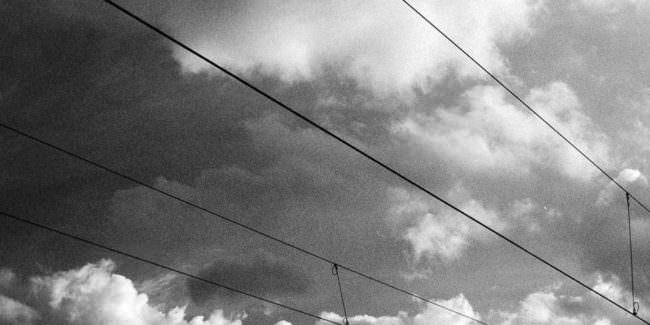 Stromleitungen vor wolkigem Himmel.