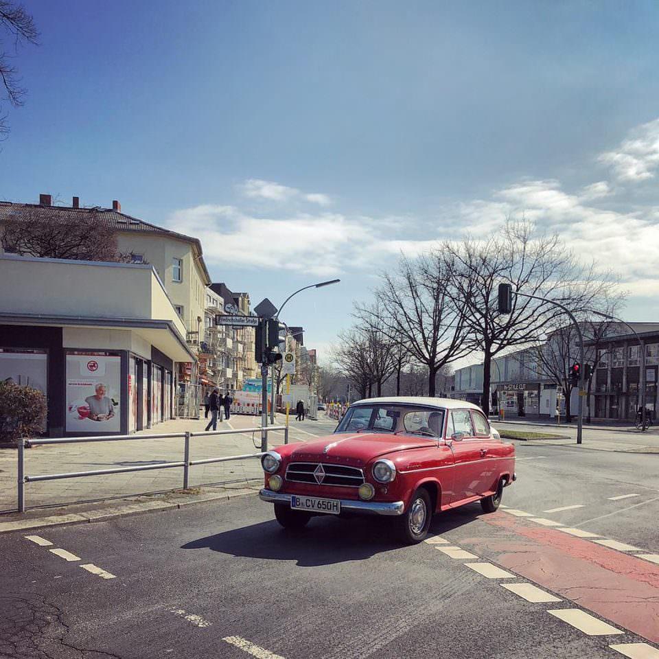 Roter Oldtimer fährt um eine Kurve in einer sommerlichen Stadt.