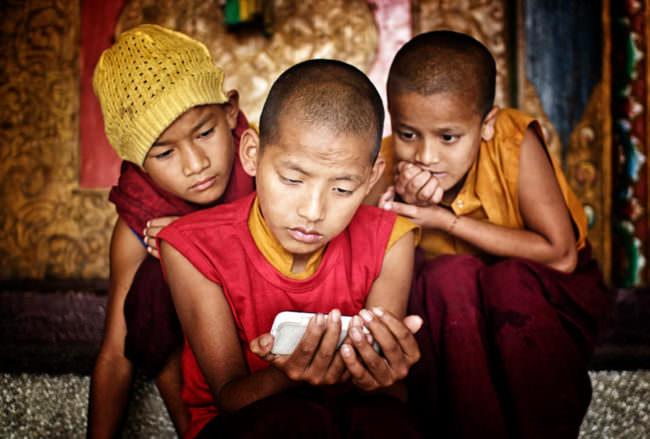 Drei Jungen schauen auf ein Handy