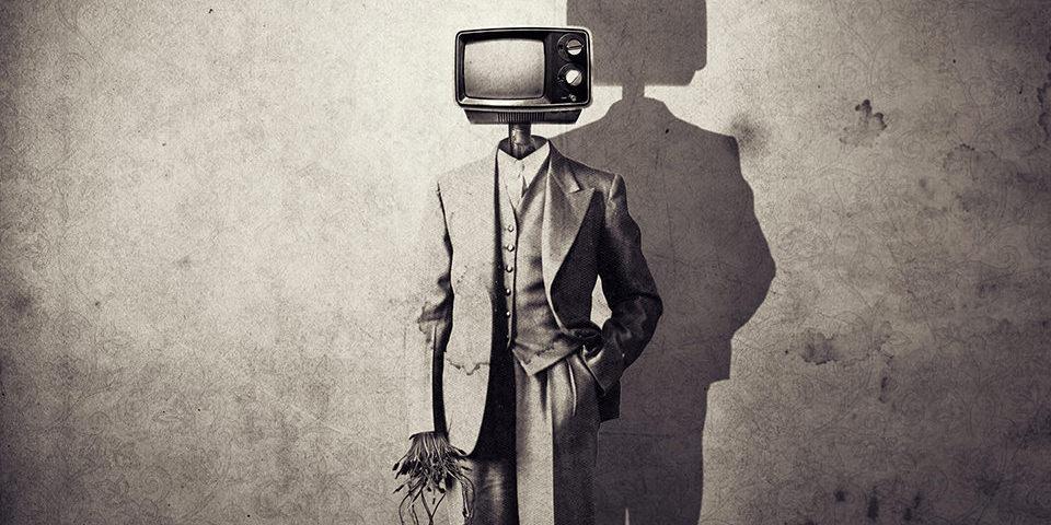 Person in Anzug mit Maschinenkopf als TVaparat mit Schatten vor einer gemusterten Wand.