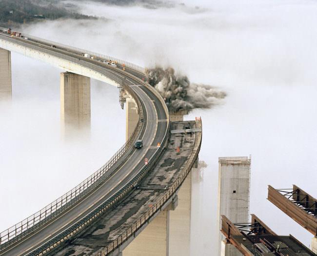 Auf Stelzen stehende Autobahnbrücke in wolkigen Höhen mit Explosionswolke an einer Stelle.