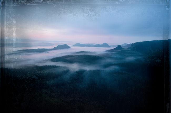 Blaue Landschaftsaufnahme mit Wolken und Bergen.