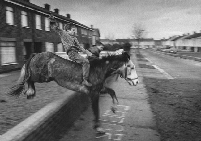 Schwarzweißbild eines springenden Ponys mit einem jungen darauf.