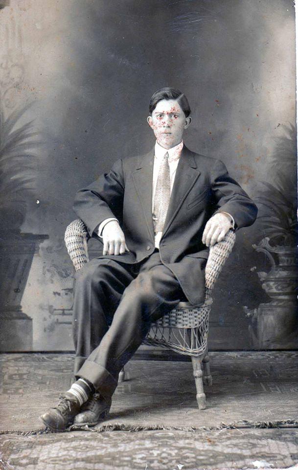 Historische Fotografie eines jungen Mannes sitzend im Anzug.