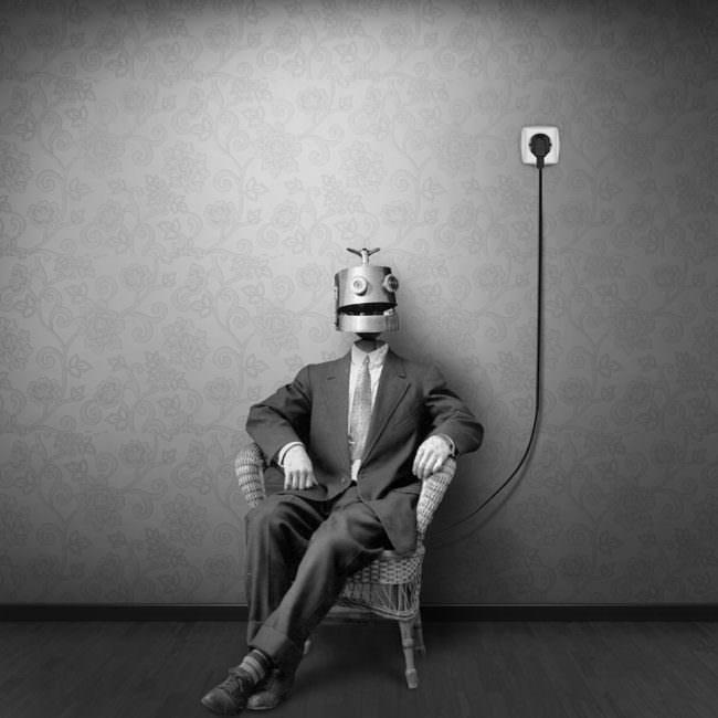 Person in Anzug mit Maschinenkopf an einer Steckdose angeschlossen, vor einer gemusterten Wand.
