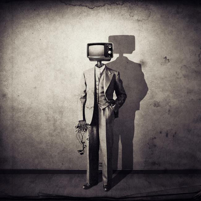 Person in Anzug mit Maschinenkopf als TV-Apparat mit Schatten vor einer gemusterten Wand.