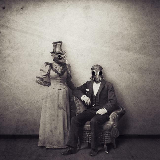 Eine Frau in Kleid mit Hut und Steampunkkopf sowie ein Herr sitzend mit Anzug und Steampunkkopf.