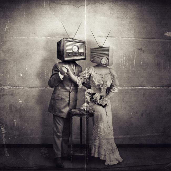 Zwei Personen stehend, eine im Anzug, eine im Kleid mit Radioköpfen.