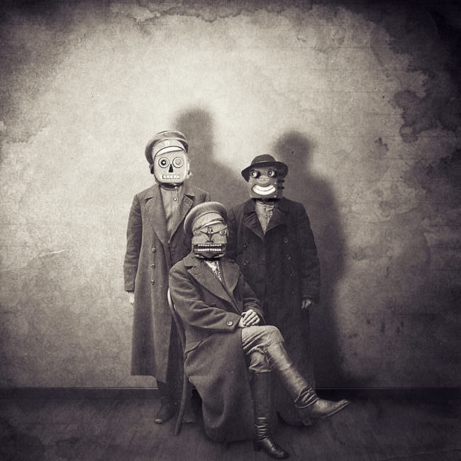 Drei Personen in älteren Mänteln mit sonderbaren Gesichtern.
