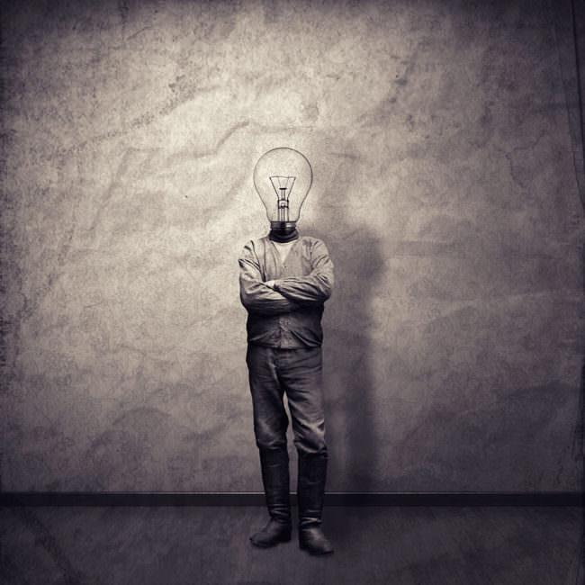 Eine Person, stehend vor einer Wand mit einer Glühbirne als Kopf und verschränkten Armen.