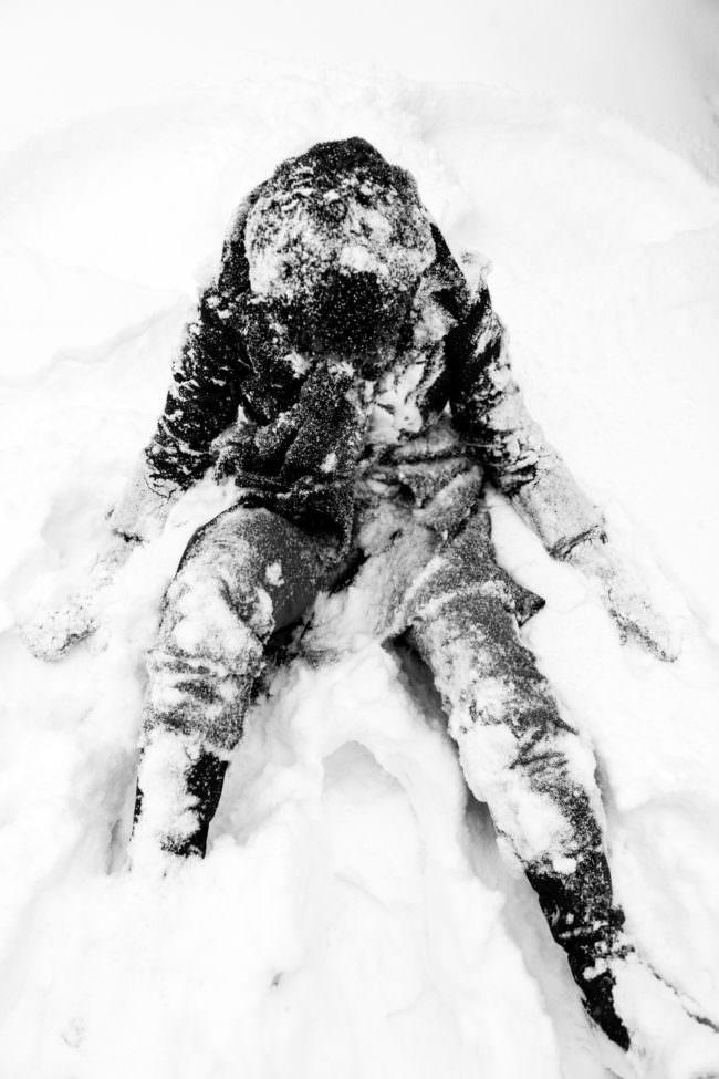 Eine schwarz gekleidete Person sitzt im Schnee