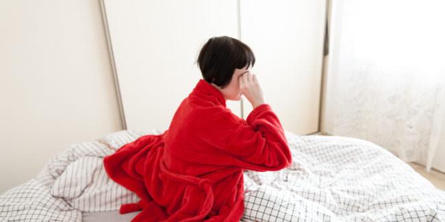 Frau im roten Bademantel sitzt in ihrem Bett