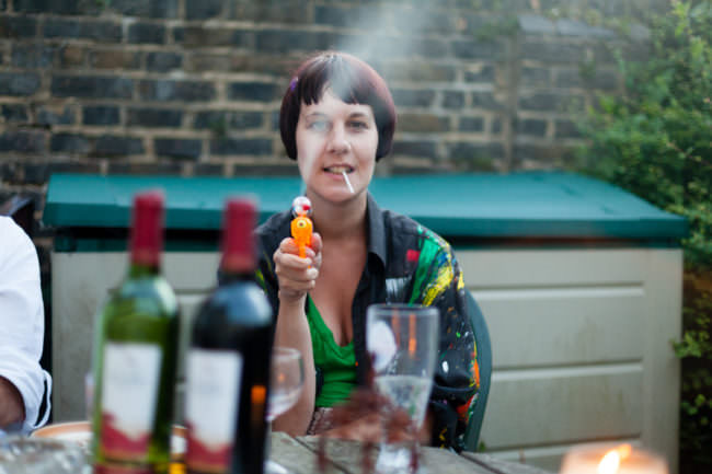 Frau mit Zigarette im Mund, die mit einer Wasserpistole schießt