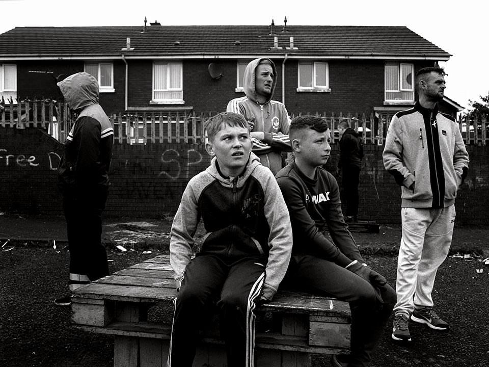 Jugendliche sitzen vor einem Haus