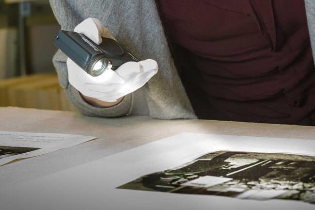 Hand in weißem Handschuh hält eine besonders geformte Lampe und leuchtet auf ein Bild.
