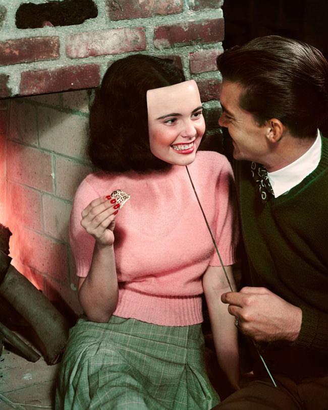 Eine junge Frau sitzend mit pinkem Pulli und ein Mann neben ihr sie anblickend in Anzug. Er hält ihr eine lächelnde Maske vor das Gesicht.