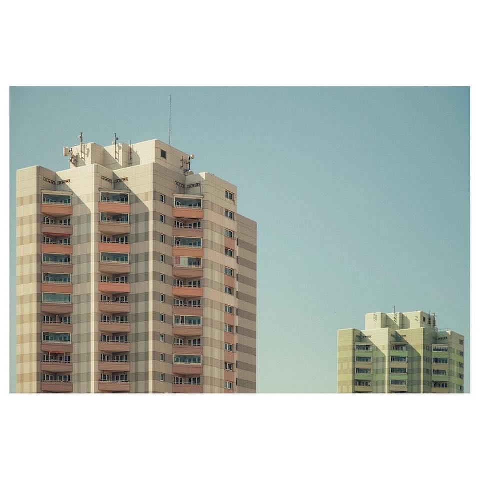 Zwei Hochhäuser, die teilweise von der Sonne angestrahlt werden.