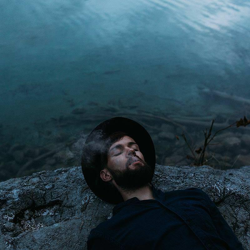Ein Mann mit Hut liegt an einem Gewässer und raucht