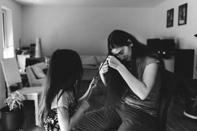 Ein Kind flechtet die Zöpfe einer Frau