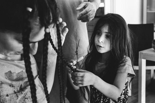Ein Kind schneidet Zöpfe einer Frau