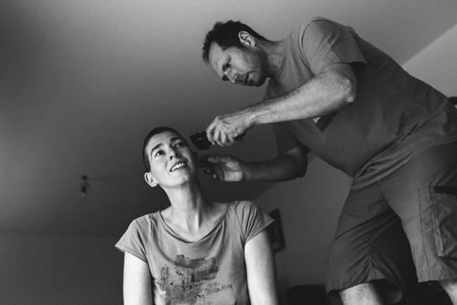 Mann rasiert Haare einer Frau