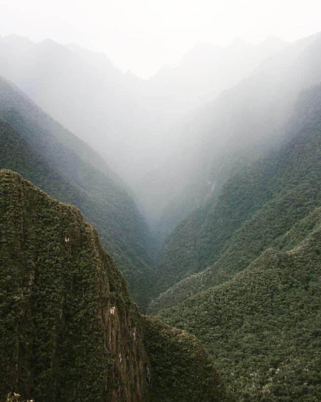 Eine Schlucht zwischen zwei Bergen mit viel Nebel.