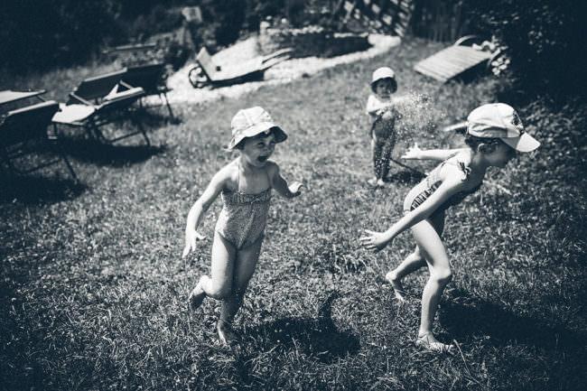 Spielende Kinder mit Wasserschlauch