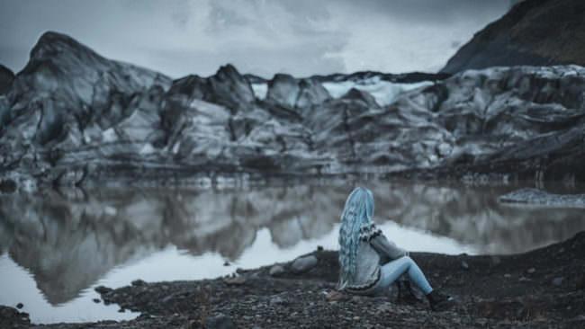 Frau sitzt vor Eisbergen