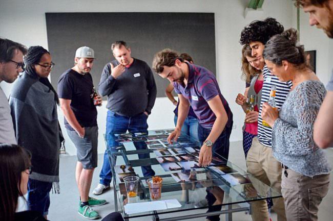 Eine Gruppe von Menschen sieht sich Bilder auf einem Glastisch an