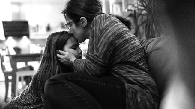 Eine Frau küsst ein Mädchen auf die Stirn