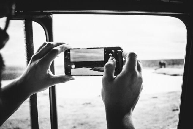 Zwei Hände halten ein Handy aus dem Autofenster